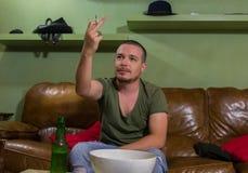 O homem está apontando o dedo médio no jogo de futebol imagem de stock royalty free