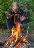 O homem está aquecendo suas mãos no fogo imagens de stock