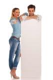 O homem está atrás do quadro de avisos vazio com mulher Fotos de Stock Royalty Free