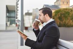 O homem está bebendo o café e está olhando no PC da tabuleta imagens de stock royalty free