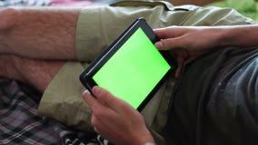 O homem está colocando no sofá em casa e no relógio na tabuleta com tela verde video estoque