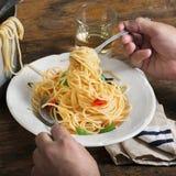 O homem está comendo a massa italiana em uma tabela de madeira rústica Fotografia de Stock Royalty Free