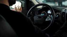 O homem está conduzindo o carro com um parque de estacionamento e e os sinais acústicos aos pedestres que andam em um lugar proib vídeos de arquivo