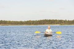 O homem está conduzindo o caiaque na água Imagens de Stock