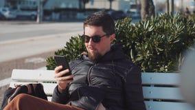 O homem está consultando pelo smartphone que senta-se fora video estoque