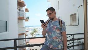 O homem está consultando redes sociais pelo smartphone exterior na cidade marinha no dia video estoque