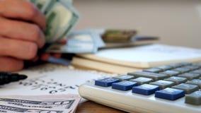 O homem está contando o dinheiro calculadora e cálculos A HOME financia o conceito video estoque