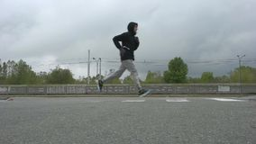 O homem está correndo ao longo da estrada video estoque