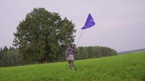 O homem está correndo com uma bandeira da União Europeia na paisagem do país Portador padrão vídeos de arquivo