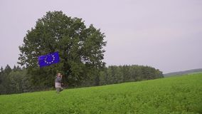 O homem está correndo com uma bandeira da União Europeia na paisagem do país Portador padrão video estoque