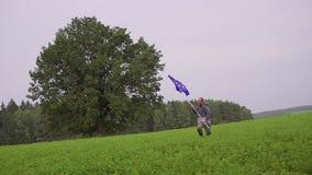 O homem está correndo com uma bandeira da União Europeia na paisagem do país Portador padrão filme