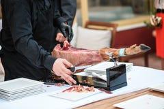 O homem está cortando o hamon Imagem de Stock