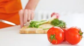 O homem está cortando vegetais maduros em uma placa de madeira no fundo Três tomates maduros no primeiro plano Imagem de Stock Royalty Free