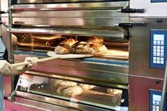 O homem está cozendo o pão no forno imagens de stock royalty free