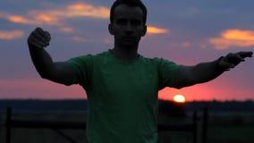 O homem está dançando: acena seus braços no fundo de um por do sol bonito Céu e silhueta vermelhos do homem filme