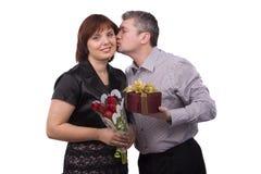 O homem está dando o presente e a mulher do beijo. foto de stock royalty free