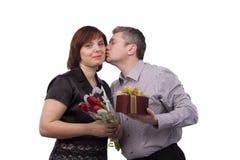 O homem está dando o presente e a mulher do beijo. fotografia de stock
