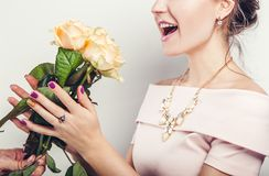 O homem está dando rosas bonitas a sua amiga entusiasmado Dia internacional do ` s das mulheres Imagem de Stock Royalty Free
