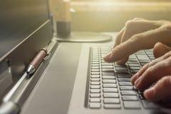 O homem está datilografando no teclado de seu portátil no escritório imagens de stock
