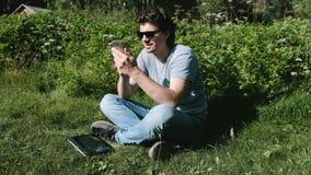 O homem está datilografando uma mensagem no telefone celular que senta-se no parque no dia ensolarado Trabalho autônomo video estoque
