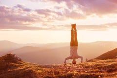 O homem está de cabeça para baixo no por do sol da montanha Imagens de Stock