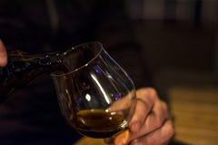 O homem está derramando a cerveja preta no vidro Fotos de Stock Royalty Free