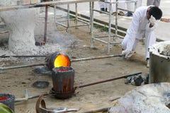 O homem está derramando o metal de derretimento na fornalha para moldar buddha s Imagens de Stock Royalty Free
