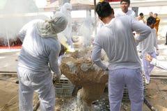 O homem está derramando o metal de derretimento na fornalha para moldar buddha s Imagem de Stock Royalty Free