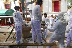 O homem está derramando o metal de derretimento na fornalha para moldar buddha s Fotografia de Stock