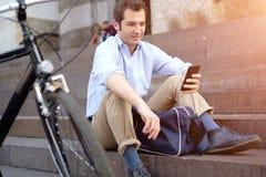 O homem está descansando ao lado de sua bicicleta e está usando o telefone Fotos de Stock Royalty Free