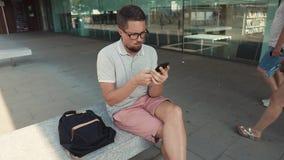 O homem está descansando o assento no banco na cidade, usando o smartphone com wifi video estoque