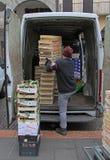 O homem está descarregando caixas com frutos em Pádua, Itália fotos de stock