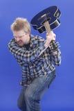 O homem está despedaçando sua guitarra no assoalho Fotos de Stock Royalty Free