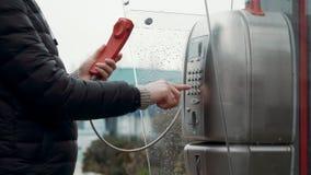 O homem está discando o número no payphone filme