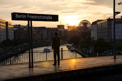 O homem está em um staion do trem na frente do Reichstag em Berlim em Alemanha foto de stock