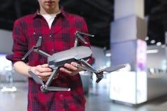 O homem está em uma loja da tecnologia e guarda um quadcopter em sua mão Comprando um quadcopter na loja da eletrônica fotos de stock royalty free