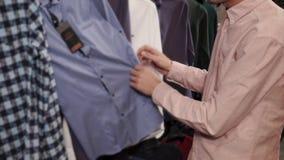 O homem está em uma loja de roupa está examinando o vestuário no gancho, encontrando camisas vídeos de arquivo