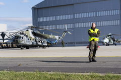 O homem está em uma pista de decolagem com o helicóptero checo de mil. Mi-171Sh das forças armadas no fundo Imagens de Stock