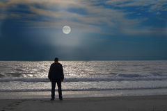O homem está em uma praia só no moonrise Fotografia de Stock Royalty Free