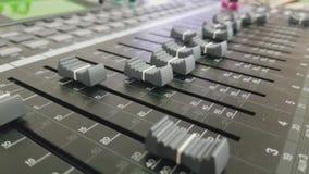 O homem está empurrando botões no misturador audio video estoque