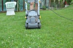 O homem está empurrando um cortador de grama Foto de Stock Royalty Free