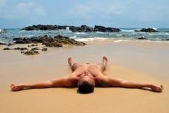 O homem está encontrando-se na areia pelo oceano Fotografia de Stock