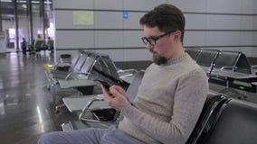 O homem está enrolando a tela do smartphone na sala de estar da partida video estoque