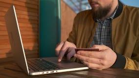 O homem está entrando o número de cartão de crédito no formulário do pagamento no local usando o portátil video estoque