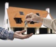 O homem está entregando uma chave da casa Imagens de Stock Royalty Free