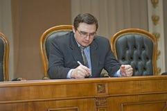 O homem está escrevendo em um papel Imagem de Stock