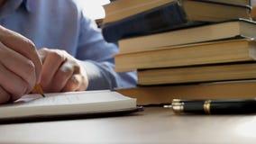 O homem está escrevendo no bloco de notas e na pilha dos livros na biblioteca Conceito da instrução e do conhecimento video estoque