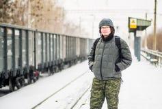O homem está esperando um trem na estação de trem fora na neve no inverno Fotografia de Stock