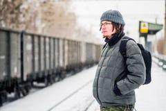 O homem está esperando um trem na estação de trem fora na neve no inverno Imagens de Stock