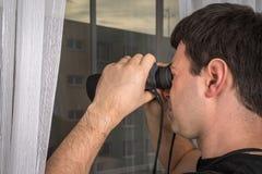 O homem está espiando seus vizinhos com binóculos fotos de stock royalty free